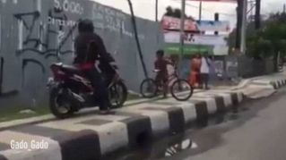 Eroico bambino indonesiano scaccia moto dal marciapiede