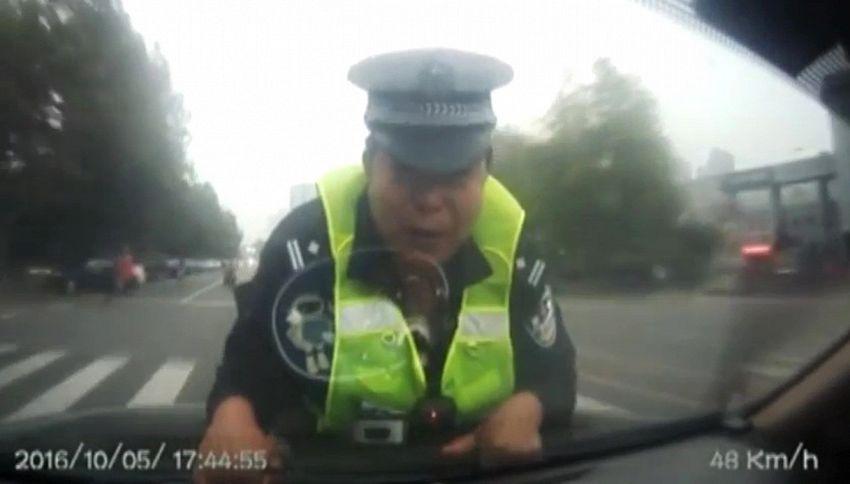 Poliziotto senza paura: due chilometri sul cofano dell'auto in fuga