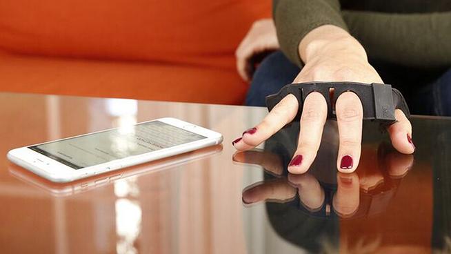 """Una tastiera indossabile che permette di scrivere un sms attraverso il movimento delle dita di una mano. Il dispositivo è stato presentato da attraverso un video pubblicato sul proprio sito internet. Il Tap Strap è una tastiera leggera di plastica con al suo interno alcuni sensori che promettono di trasformare in lettere il movimento delle dita. In questo modo sarà poTapssibile scrivere usando qualsiasi superficie come virtual keyboard. A ogni digitazione corrisponderà una lettera che apparirà sullo schermo via Bluetooth. Oltre alle lettere il device permetterà di poter inserire punti, virgole e altri elementi della punteggiatura, compresi i caratteri speciali. Il testo potrà essere inviato oltre che al display dello smarphone anche su un visore VR. Come funziona Il dispositivo ancora non è stato lanciato sul mercato quindi per il funzionamento dobbiamo affidarci a quanto è scritto sul sito. Il device ha una serie di sensori inseriti al suo interno che monitorano i movimenti delle dita. Le informazioni, sempre secondo quanto scrive l'azienda, vengono poi analizzati da un chip che decodifica i comandi e li trasforma in caratteri. Successivamente i dati vengono inviati al telefono. Il Tap Strap può essere indossato su entrambi le mani, l'importante è che il device sia posizionato sulla parte bassa delle dita. Per avviare il meccanismo bisognerà digitare tre volte su una superficie piana. Il device se apparentemente sembra di velocizzare e semplificare la scrittura di messaggi solleva alcuni dubbi. Se come dice l'azienda ad ogni tocco corrisponderà un carattere, una persona che vuole scrivere un messaggio dovrà indubbiamente memorizzare un certo numero di combinazioni. Tap Strap metterà comunque a disposizione un'app attraverso cui esercitarsi. """"Il metodo migliore per acquisire una certa dimestichezza con il dispositivo è scaricare Tap Genius e iniziare a giocare per diventare i più veloci possibile"""", scrive l'azienda. Per adesso non si hanno notizie sul prezzo e su qu"""
