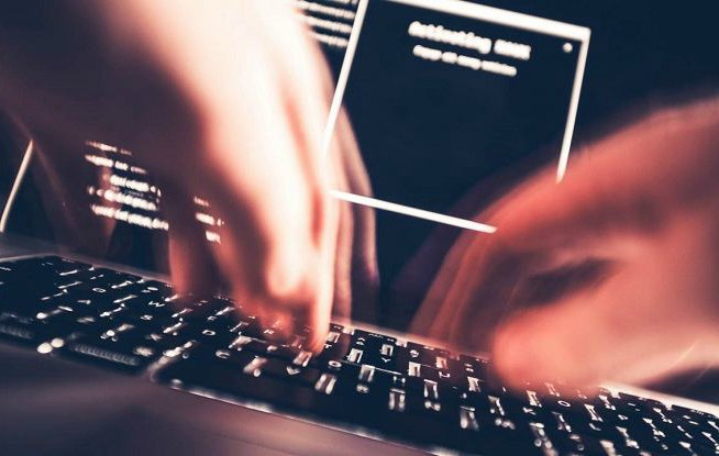 Hacker digita tastiera di un laptop